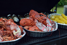 Lobster, corn, and baked potato on the grill and ready to serve